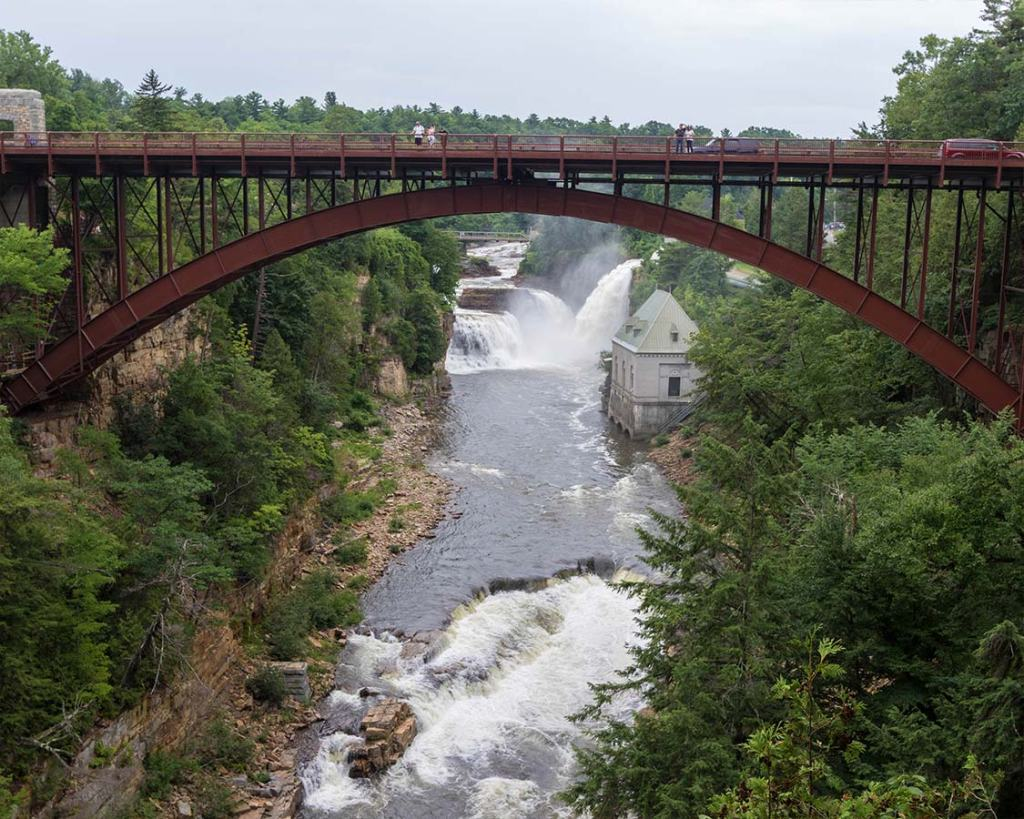 Picture shows a bridge over a large chasm with rapids flowing underneath.
